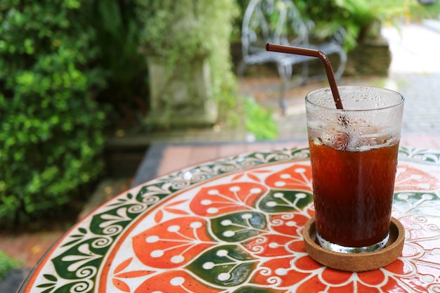 パティオでカラフルなタイル張りのテーブルにアイスコーヒーを半分ガラス