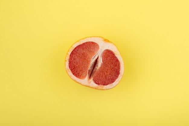 黄色い表面に半分のグレープフルーツ