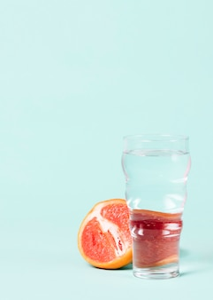 Half of grapefruit with glass of water