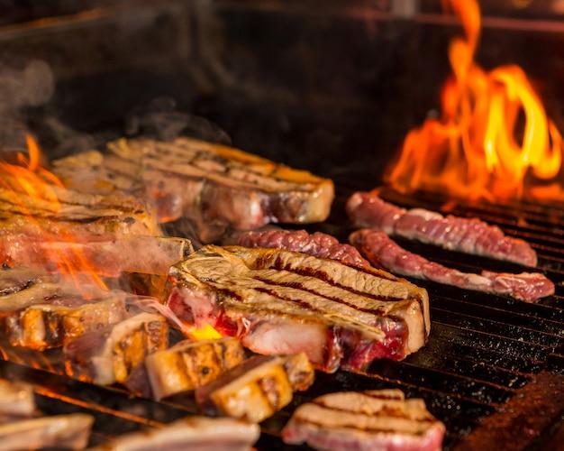 グリルで半分焼き、半分準備ができた生ステーキ