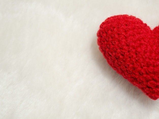 Half of handmade red yarn heart on white wool