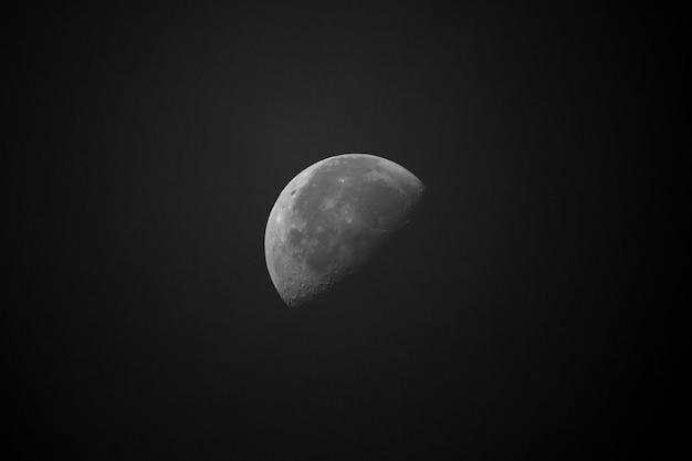 Half illuminated moon on black sky