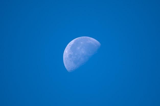 Half illuminated moon on blue sky