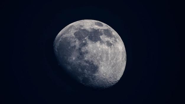 青い空を背景に半分照らされた月