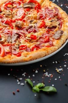 Half of italian pizza and fresh basil leaves