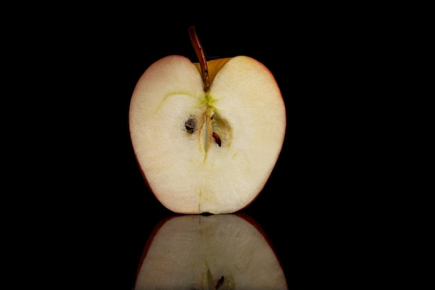 Half a juicy apple on a black wall with reflection. close-up. healthy lifestyle and vegetarianism.