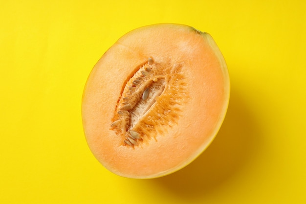 Half of juicy melon on yellow background