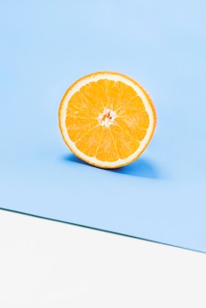 Half of juicy orange on white and blue background