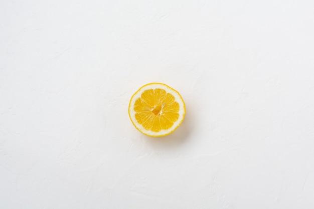 白い石またはコンクリートの古い背景にハーフレモン。上面図。