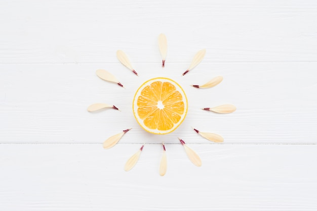 Half of lemon with petals on white background