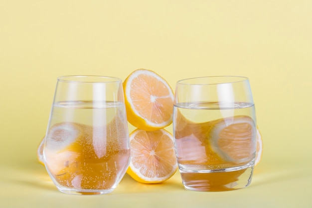 Half lemons and water glasses on yellow background
