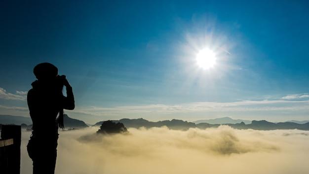 長い髪の写真家の女性の半分の長さは、山の日の出と朝の景色の写真を撮ります。