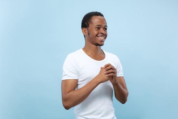 절반 길이 파란색 배경에 흰색 셔츠에 젊은 아프리카 계 미국인 남성 모델의 초상화를 닫습니다. 인간의 감정, 표정, 광고 개념. 의심, 질문, 불확실성, 미소.