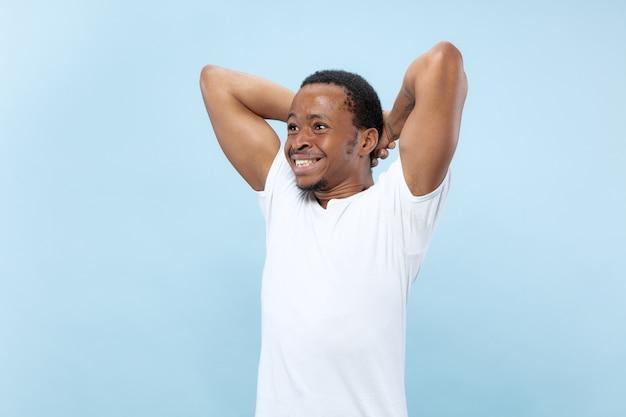 青い壁に白いシャツを着た若いアフリカ系アメリカ人男性モデルのハーフレングスのクローズアップの肖像画。人間の感情、顔の表情、広告または賭けの概念。ショックを受け、興奮し、驚いた。