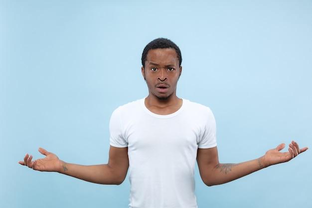 절반 길이 파란색 배경에 흰색 셔츠에 젊은 아프리카 계 미국인 남자의 초상화를 닫습니다. 인간의 감정, 표정, 광고 개념. 질문과 불확실성, 의심, 부정적인 감정.