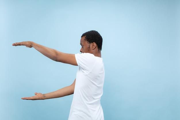 절반 길이 파란색 배경에 흰색 셔츠에 젊은 아프리카 계 미국인 남자의 초상화를 닫습니다. 인간의 감정, 표정, 광고 개념. 빈 바, copyspace 텍스트를 들고.