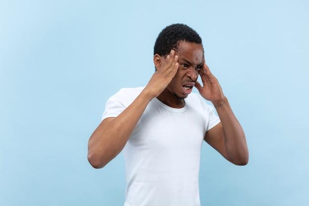 절반 길이 파란색 배경에 흰색 셔츠에 젊은 아프리카 계 미국인 남자의 초상화를 닫습니다. 인간의 감정, 표정, 광고 개념. 두통, 무거운 생각, 정신적 문제로 고통받습니다.