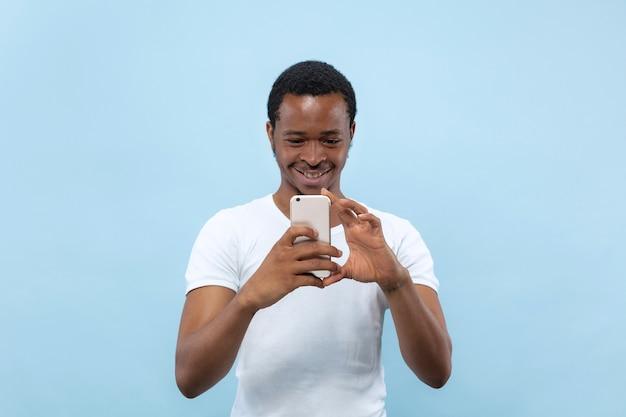 青の背景に白いシャツを着た若いアフリカ系アメリカ人の男性の半分の長さのクローズアップの肖像画。人間の感情、顔の表情、広告のコンセプト。彼のスマートフォンで写真やvlogのコンテンツを撮る。