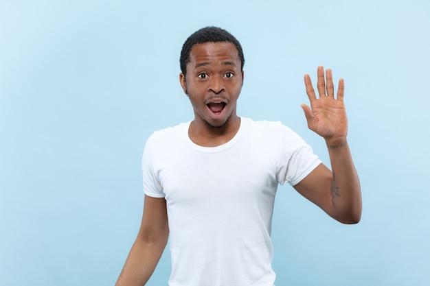 절반 길이 파란색 배경에 흰색 셔츠에 젊은 아프리카 계 미국인 남자의 초상화를 닫습니다. 인간의 감정, 표정, 광고, 판매 개념. 누군가를 만나고, 인사하고, 초대합니다.