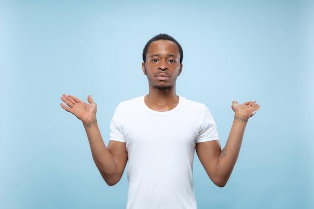 青いスペースに白いシャツを着た若いアフリカ系アメリカ人男性のハーフレングスのクローズアップの肖像画。人間の感情、表情、広告、コンセプト