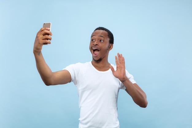 Поясной крупным планом портрет молодого афро-американского человека в белой рубашке на синем пространстве