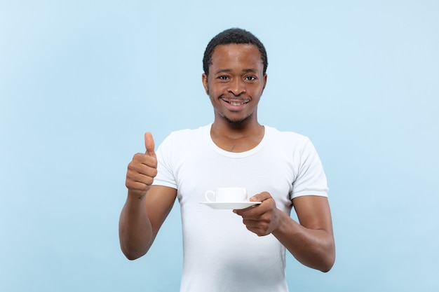 青いスペースに白いシャツを着た若いアフリカ系アメリカ人男性のハーフレングスのクローズアップの肖像画