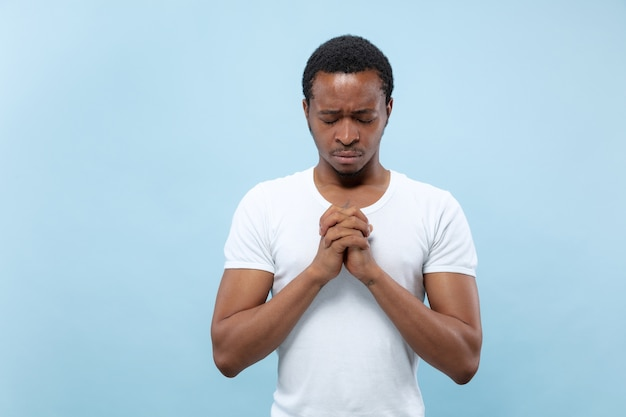 절반 길이 푸른 공간에 흰 셔츠에 젊은 아프리카 계 미국인 남자의 초상화를 닫습니다.