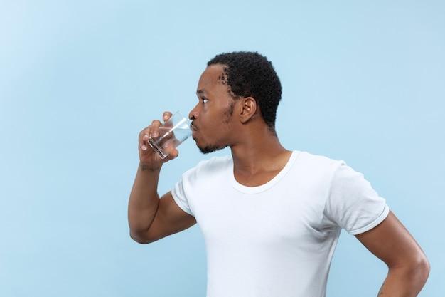 青い壁に白いシャツを着た若いアフリカ系アメリカ人男性のハーフレングスのクローズアップの肖像画。人間の感情、顔の表情、広告のコンセプト。コップと飲料水を持っています。