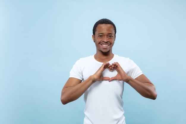 青い壁に白いシャツを着た若いアフリカ系アメリカ人男性のハーフレングスのクローズアップの肖像画。人間の感情、顔の表情、広告のコンセプト。彼の手でハートのサインを見せて、笑っています。
