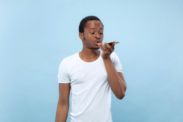 青い壁に白いシャツを着た若いアフリカ系アメリカ人男性のハーフレングスのクローズアップの肖像画。人間の感情、顔の表情、広告のコンセプト。スマートフォンで話したり、音声メッセージを録音したりします。
