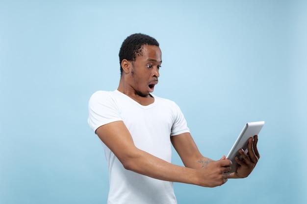 青い壁に白いシャツを着た若いアフリカ系アメリカ人男性のハーフレングスのクローズアップの肖像画。人間の感情、表情、広告、販売、コンセプト。タブレットを使用して、ショックを受け、驚いた。