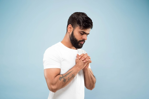 半分の長さのクローズアップの肖像画は、青い背景で隔離の白いシャツを着た若いヒンドゥー教の男の肖像画です。人間の感情、顔の表情、広告のコンセプト。ネガティブスペース。目を閉じて立って祈る。