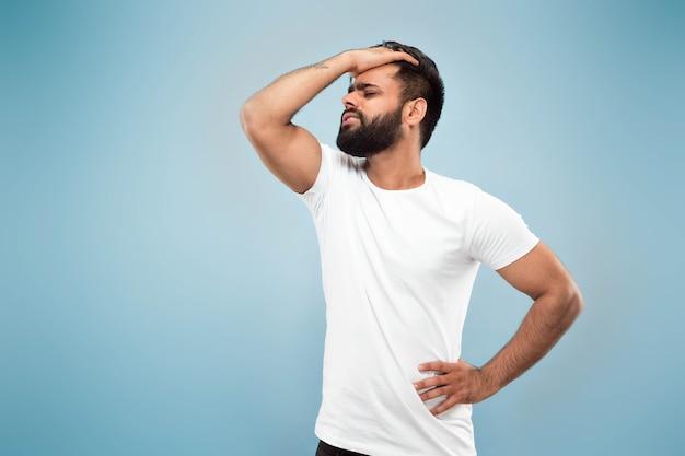 青いスペースに分離された白いシャツを着た若いヒンドゥー教の男のハーフレングスのクローズアップの肖像画