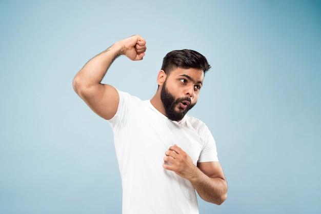 절반 길이 파란색 배경에 흰색 셔츠에 젊은 힌두교 남자의 초상화를 닫습니다. 인간의 감정, 표정, 광고 개념. 부정적인 공간. 축하하고, 승리하고, 미친 행복합니다.