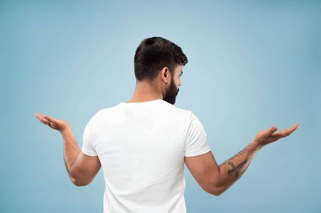 ハーフレングスは、青い背景に白いシャツを着た若いヒンドゥー教の男の肖像画をクローズアップします。人間の感情、顔の表情、広告のコンセプト。ネガティブスペース。空のバーを表示し、指さし、選択し、招待します。