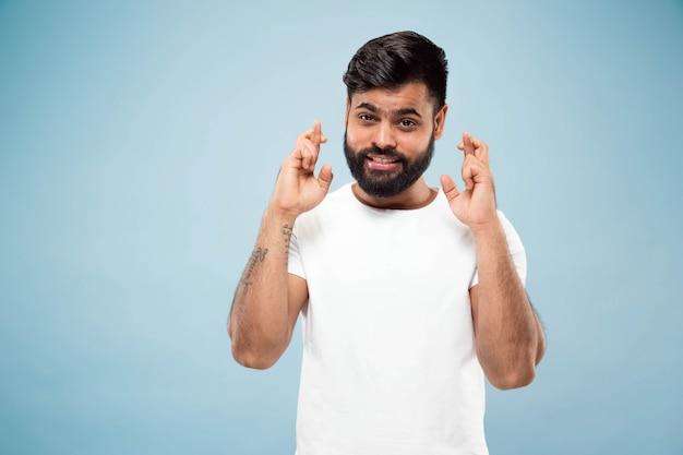절반 길이 파란색 배경에 흰색 셔츠에 젊은 힌두교 남자의 초상화를 닫습니다. 인간의 감정, 표정, 광고 개념. 부정적인 공간. 행운의 징조를 보여주는 미소.