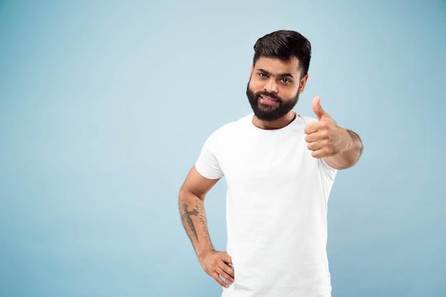 Поясной конец вверх по портрету молодого индусского человека в белой рубашке на синем фоне. человеческие эмоции, выражение лица, концепция рекламы. негативное пространство. демонстрирует знак ок, хорошо, отлично. улыбается.