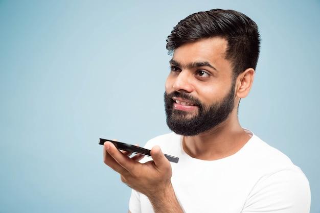 절반 길이 파란색 배경에 흰색 셔츠에 젊은 힌두교 남자의 초상화를 닫습니다. 인간의 감정, 표정, 광고 개념. 부정적인 공간. 휴대폰으로 말하고 음성 메시지를 녹음합니다.