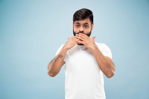 ハーフレングスは、青い背景に白いシャツを着た若いヒンドゥー教の男の肖像画をクローズアップします。人間の感情、顔の表情、販売、広告のコンセプト。ネガティブスペース。手で顔を覆う。