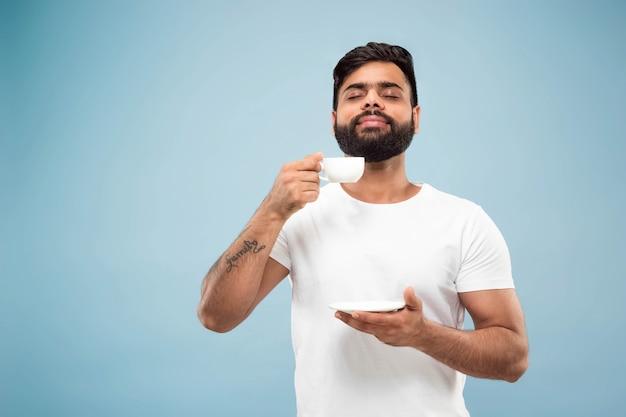 ハーフレングスは、青い背景に白いシャツを着た若いヒンドゥー教の男の肖像画をクローズアップします。人間の感情、顔の表情、販売、広告のコンセプト。ネガティブスペース。コーヒーやお茶を楽しむ。