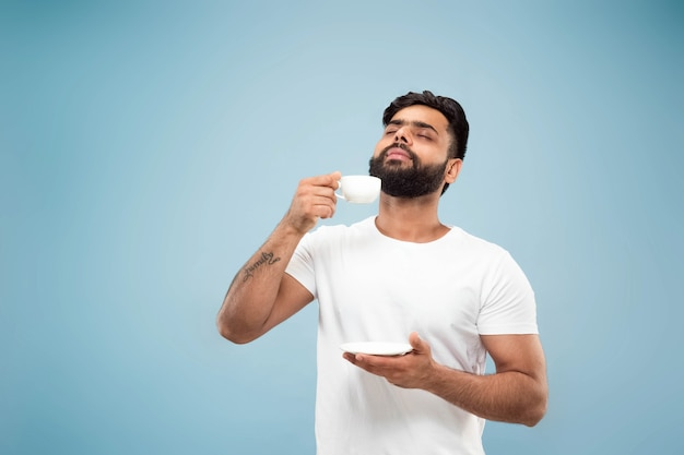 절반 길이 파란색 배경에 흰색 셔츠에 젊은 힌두교 남자의 초상화를 닫습니다. 인간의 감정, 표정, 판매, 광고 개념. 부정적인 공간. 커피 나 차를 마시 며 즐기기.