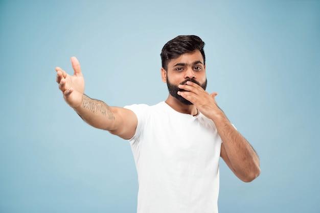 절반 길이 파란색 배경에 흰색 셔츠에 젊은 힌두교 남자의 초상화를 닫습니다. 인간의 감정, 표정, 판매, 광고 개념. 부정적인 공간. 행복하고 놀라움을 나타냅니다.