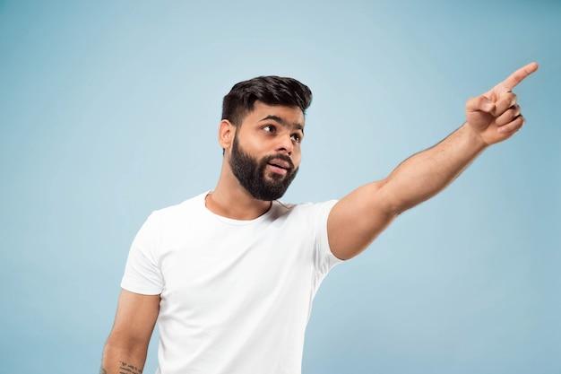 절반 길이 파란색 배경에 흰색 셔츠에 젊은 힌두교 남자의 초상화를 닫습니다. 인간의 감정, 표정, 판매, 광고 개념. 부정적인 공간. 충격과 놀라움을 지적합니다.