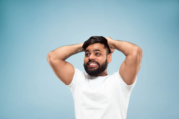 절반 길이 파란색 배경에 흰색 셔츠에 젊은 힌두교 남자의 초상화를 닫습니다. 인간의 감정, 표정, 판매, 광고 개념. 부정적인 공간. 충격, 경악 또는 미친 행복한 감정.