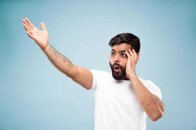 青いスペースに白いシャツを着た若いヒンドゥー教の男のハーフレングスのクローズアップの肖像画。人間の感情、表情、販売、広告コンセプト。ネガティブスペース