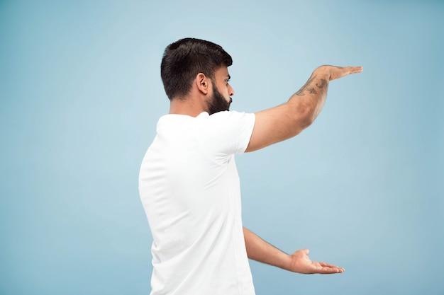 절반 길이 푸른 공간에 흰 셔츠에 젊은 힌두교 남자의 초상화를 닫습니다
