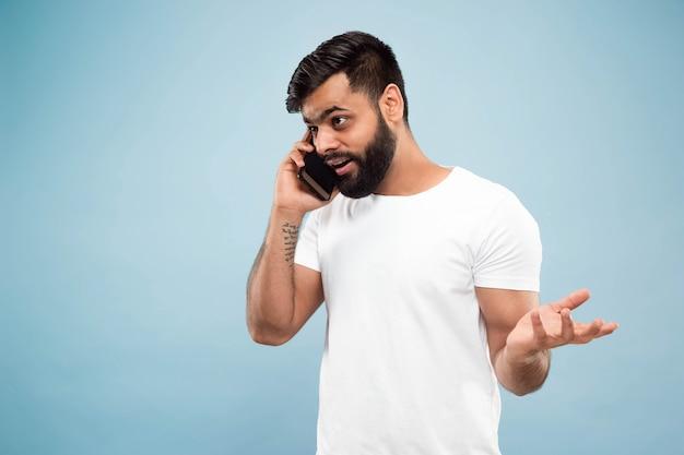 青いスペースに白いシャツを着た若いヒンドゥー教の男のハーフレングスのクローズアップの肖像画