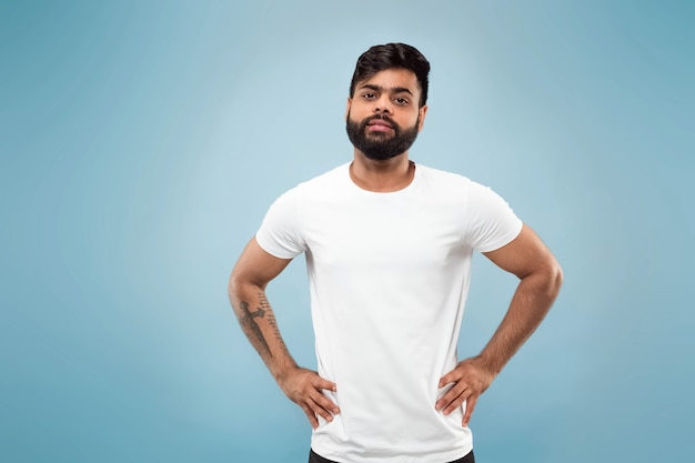 Поясной конец вверх по портрету молодого человека индуизма в белой рубашке на голубой стене. человеческие эмоции, выражение лица, концепция рекламы. негативное пространство. позирует, стоит и улыбается, выглядит спокойно.