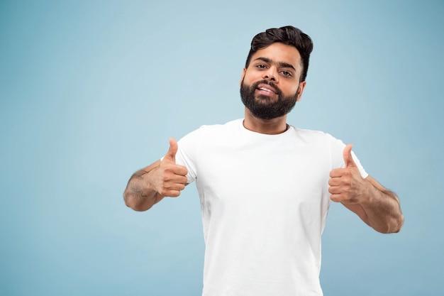 절반 길이 파란 벽에 흰 셔츠에 젊은 힌두교 남자의 초상화를 닫습니다. 인간의 감정, 표정, 광고 개념. 부정적인 공간. 좋아요, 좋아요, 좋아요. 웃고.