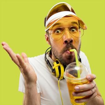 シャツを着た若い男のハーフレングスのクローズアップの肖像画。ヘッドフォンと飲み物を持つ男性モデル。人間の感情、表情、夏、週末のコンセプト。面白い飲酒。